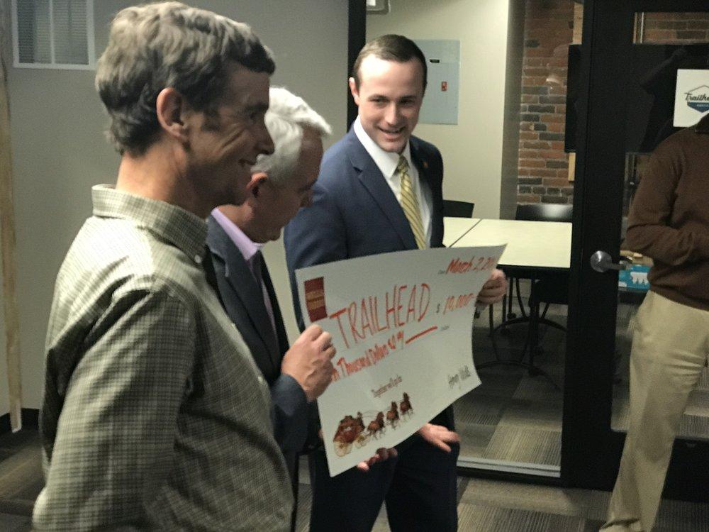 Trailhead's Raino Zoller grins as Boise Mayor Dave Bieter recieves a check from Wells Fargo's Flip Kleffner